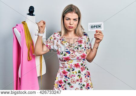 Beautiful caucasian woman dressmaker designer holding open sign annoyed and frustrated shouting with anger, yelling crazy with anger and hand raised
