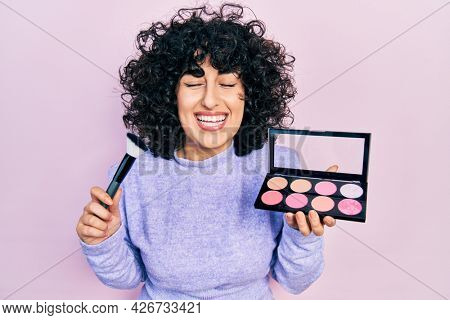 Young middle east woman holding makeup brush and blush smiling and laughing hard out loud because funny crazy joke.