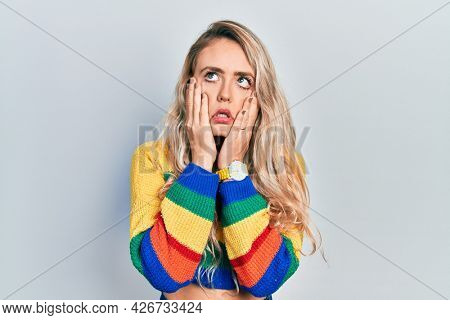 Beautiful young blonde woman wearing colored sweater tired hands covering face, depression and sadness, upset and irritated for problem