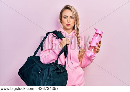 Beautiful young blonde woman holding gym bag and water bottle puffing cheeks with funny face. mouth inflated with air, catching air.