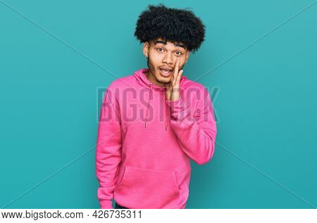 Young african american man with afro hair wearing casual pink sweatshirt hand on mouth telling secret rumor, whispering malicious talk conversation