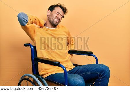 Handsome man with beard sitting on wheelchair suffering of neck ache injury, touching neck with hand, muscular pain