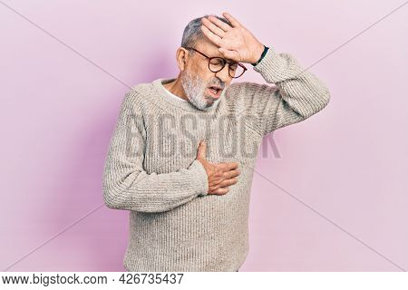 Handsome senior man with beard wearing casual sweater and glasses touching forehead for illness and fever, flu and cold, virus sick
