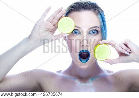 Surprised Caucasian Female With Smooth Skin Wearing Teeth Brackets. Posing With Green Lime In Hand A