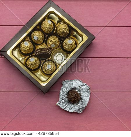 The Brown Cardboard Box Is Filled With Chocolate Candies, Wrapped In A Golden Foil. One Candy Deploy