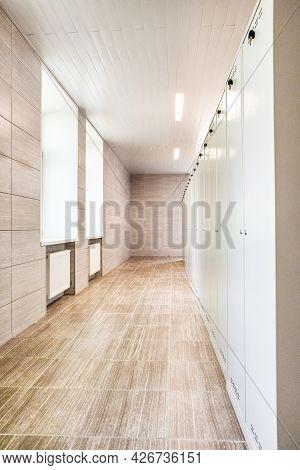 Indoors View Of Long Industrial Tile Corridor With Metal Lockers.