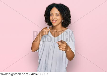 Young african american girl wearing casual clothes pointing fingers to camera with happy and funny face. good energy and vibes.