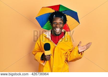Young african american journalist man wearing yellow raincoat and umbrella cap celebrating victory with happy smile and winner expression with raised hands