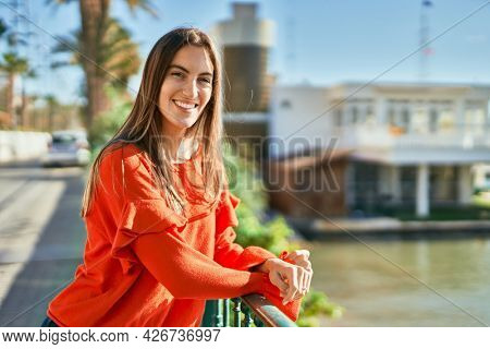 Young hispanic woman smiling happy leaning on balustrade.