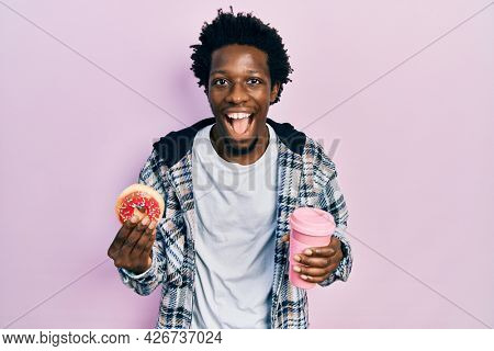 Young african american man eating doughnut and drinking coffee smiling and laughing hard out loud because funny crazy joke.