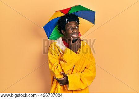 Young african american man wearing yellow raincoat thinking worried about a question, concerned and nervous with hand on chin