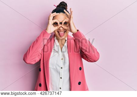 Beautiful middle eastern woman wearing business jacket and glasses doing ok gesture like binoculars sticking tongue out, eyes looking through fingers. crazy expression.