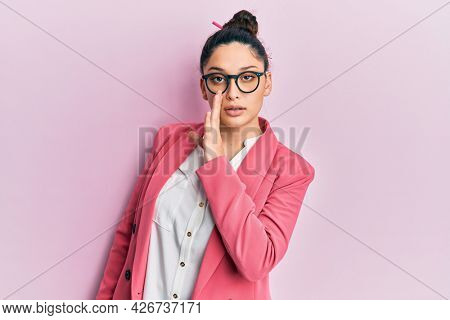 Beautiful middle eastern woman wearing business jacket and glasses hand on mouth telling secret rumor, whispering malicious talk conversation