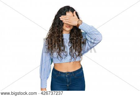 Young hispanic girl wearing casual clothes covering eyes with hand, looking serious and sad. sightless, hiding and rejection concept