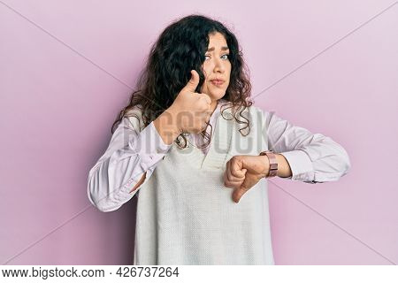 Young brunette woman with curly hair wearing casual clothes doing thumbs up and down, disagreement and agreement expression. crazy conflict