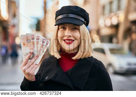 Young blonde woman smiling happy holding united kingdom pounds banknotes at the city.