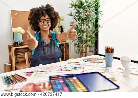 Beautiful african american woman with afro hair painting at art studio approving doing positive gesture with hand, thumbs up smiling and happy for success. winner gesture.