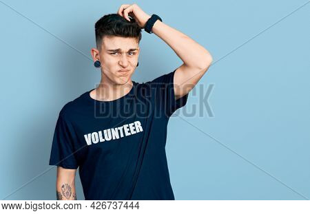 Young caucasian boy with ears dilation wearing volunteer t shirt confuse and wondering about question. uncertain with doubt, thinking with hand on head. pensive concept.