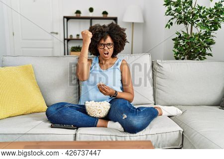 African american woman with afro hair sitting on the sofa eating popcorn at home annoyed and frustrated shouting with anger, yelling crazy with anger and hand raised
