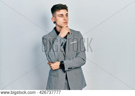 Young caucasian boy with ears dilation wearing business jacket with hand on chin thinking about question, pensive expression. smiling with thoughtful face. doubt concept.