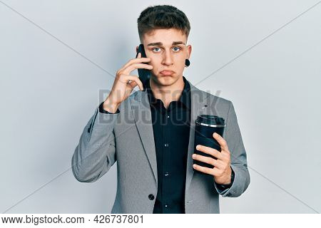 Young caucasian boy with ears dilation using smartphone and drinking a cup of coffee depressed and worry for distress, crying angry and afraid. sad expression.