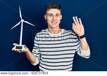 Young caucasian boy with ears dilation holding solar windmill for renewable electricity doing ok sign with fingers, smiling friendly gesturing excellent symbol