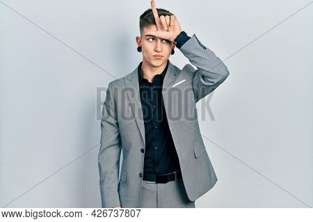 Young caucasian boy with ears dilation wearing business jacket making fun of people with fingers on forehead doing loser gesture mocking and insulting.