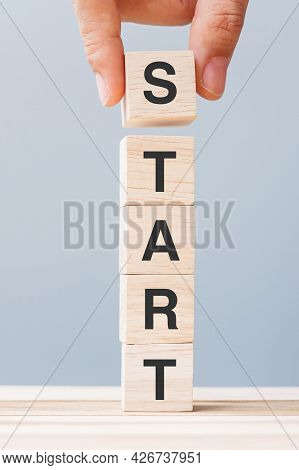 Business Man Hand Holding Wooden Block With Start Text On Table Background. Goals, Mindset , Strateg
