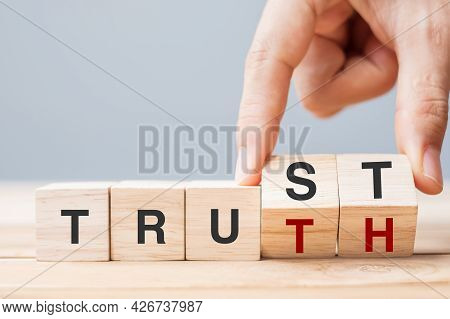 Business Man Hand Change Wooden Cube Block With Trust And Truth Business Word On Table Background. T