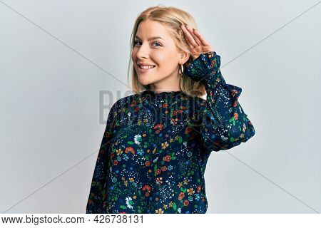 Young blonde woman wearing casual clothes smiling with hand over ear listening an hearing to rumor or gossip. deafness concept.