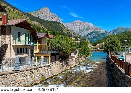 Alpine river flow through small town as mountains under blue sky in background in Piedmont, Northern Italy.