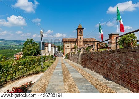 Narrow cobblestone walkway along brick wall as small parish church under beautiful sky on background in town of Grinzane Cavour in Piedmont, Northern Italy.