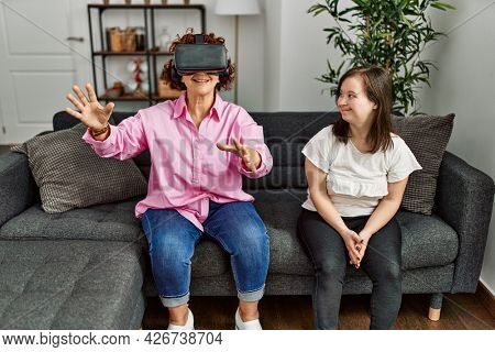 Mature mother and down syndrome daughter at home playing virtual reality video games