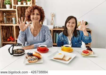 Family of mother and down syndrome daughter sitting at home eating breakfast showing and pointing up with fingers number ten while smiling confident and happy.