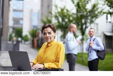 Business And Finance Industry Concept. Young Attractive Businesswoman In Yellow Blouse Standing Outd