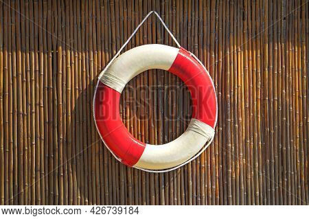 Red Lifebuoy Pool Ring Hanging On A Bamboo Wall For Emergency Response, When People Submerging In Th