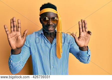 Handsome black man drunk wearing tie over head and sunglasses showing and pointing up with fingers number nine while smiling confident and happy.