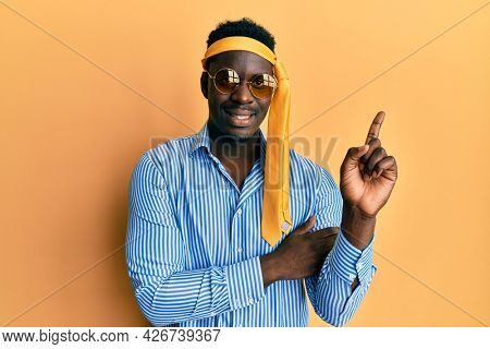 Handsome black man drunk wearing tie over head and sunglasses with a big smile on face, pointing with hand and finger to the side looking at the camera.