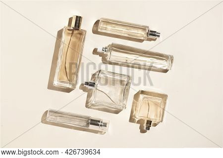 Perfume Bottles Of Beige Color. Flatlay Still Life In The Style Of Minimalism On A Cream Background,