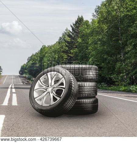 Summer Tires And Alloy Wheels Set On An Asphalt Road. Tire Change Season, Auto Trade, Copy Space, Sq