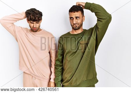 Young gay couple standing over isolated white background confuse and wonder about question. uncertain with doubt, thinking with hand on head. pensive concept.