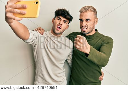 Homosexual gay couple standing together taking a selfie photo with smartphone annoyed and frustrated shouting with anger, yelling crazy with anger and hand raised