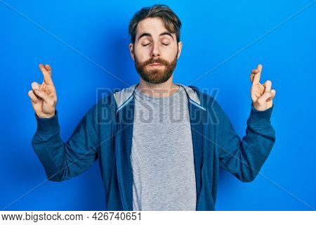 Caucasian man with beard wearing casual sweatshirt gesturing finger crossed smiling with hope and eyes closed. luck and superstitious concept.