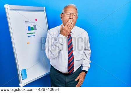 Senior man with grey hair standing by business blackboard bored yawning tired covering mouth with hand. restless and sleepiness.