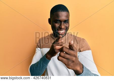 Young african american man wearing casual clothes pointing fingers to camera with happy and funny face. good energy and vibes.