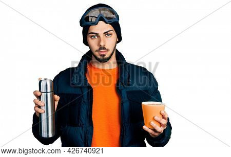 Young hispanic man with beard wearing snow wear and sky glasses holding coffee and thermo relaxed with serious expression on face. simple and natural looking at the camera.