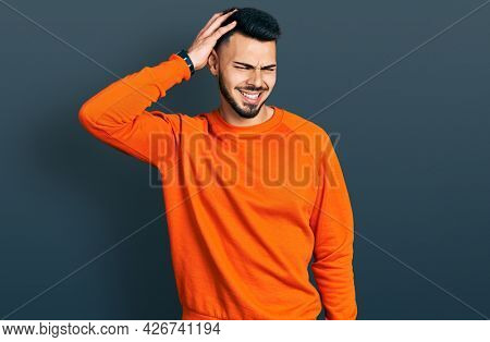 Young hispanic man with beard wearing casual orange sweater confuse and wonder about question. uncertain with doubt, thinking with hand on head. pensive concept.