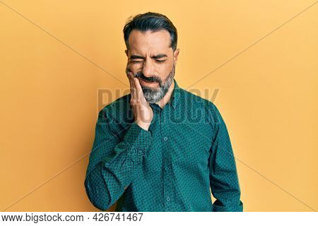 Middle age man with beard and grey hair wearing business clothes touching mouth with hand with painful expression because of toothache or dental illness on teeth. dentist