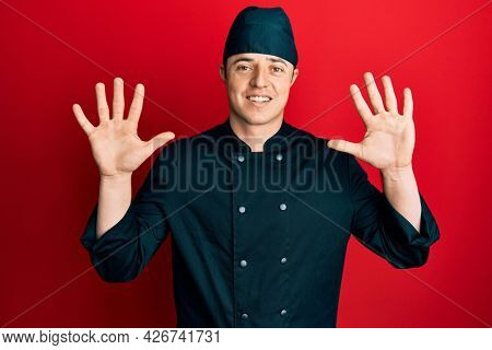 Handsome young man wearing professional cook uniform and hat showing and pointing up with fingers number ten while smiling confident and happy.