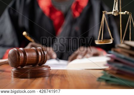 Focus On Judge Gavel, Unrecognizable Judge Busy Writing Verdict Or Making Notes From The Book With G